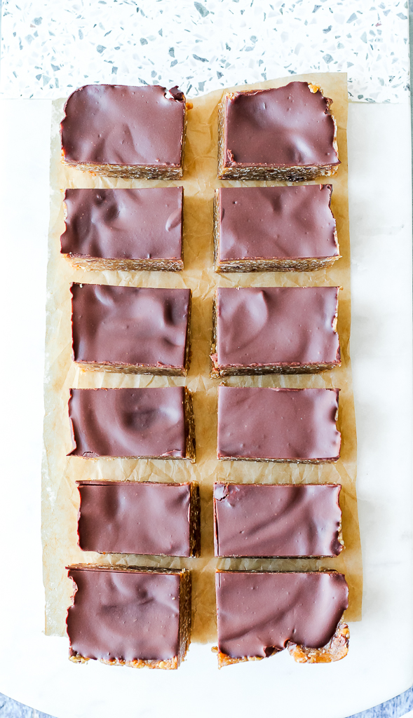 an overhead shot of the twelve cookie dough bars on a white marble board