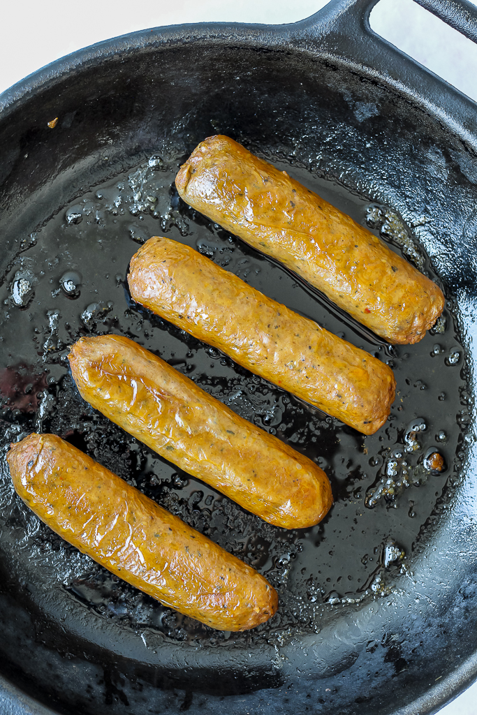 overhead shot of the beyond sausages in a cast iron skillet