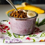 straight on shot of a blueberry chia pudding breakfast bowl in a clear Weck jar set on a marble board with a blue background