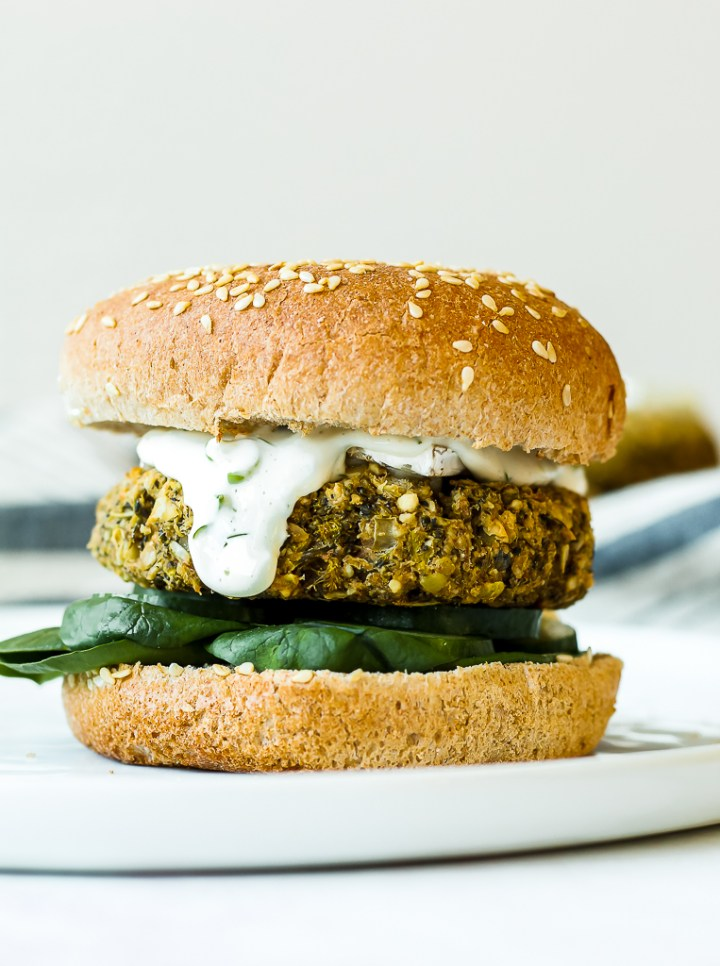 straight on shot of a broccoli white bean burger on a whole grain bun with cucumber, spinach, brie, and lemon dill aioli