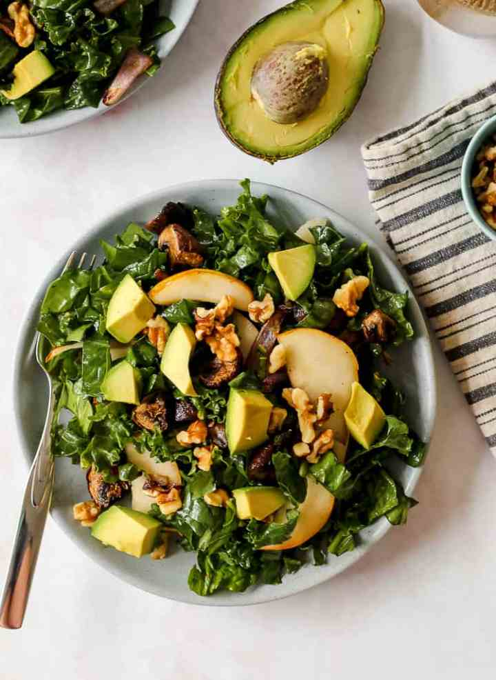 overhead shot of a serving of spinach salad with roasted mushrooms, walnuts, avocado, and pear on a blue plate