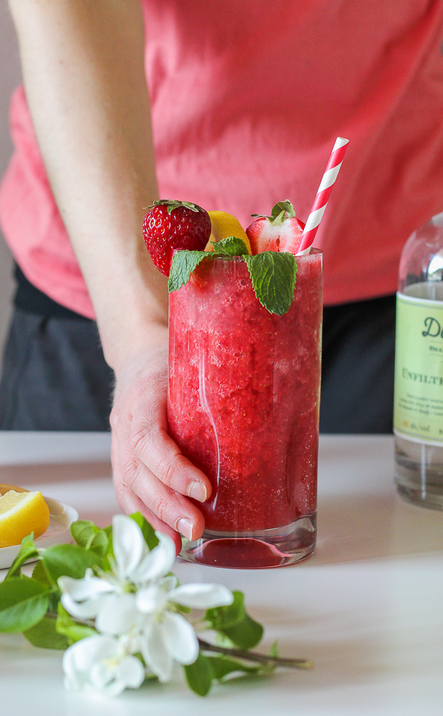 straight on shot of boozy strawberry lemonade kombucha crush in a tall glass garnished with strawberries, lemon and mint in someone's hand