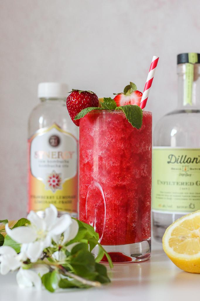 straight on shot of the strawberry kombucha crush on a white table with bottles of kombucha and gin around it