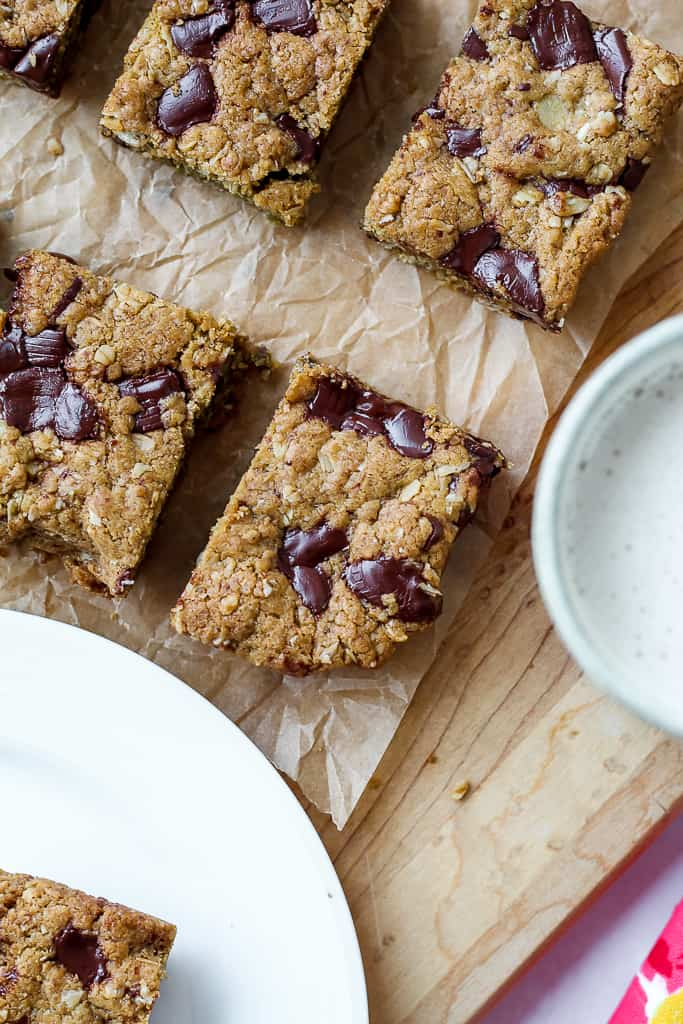 an overhead shot of a few vegan chocolate chunk oatmeal cookie bars on a wooden board and a glass of almond milk