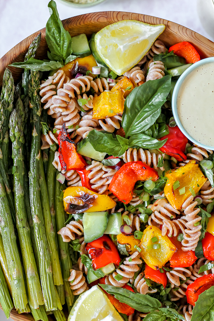 close up overhead photo of the pasta salad in a big wooden bowl with a small dish of the tahini dressing on the side