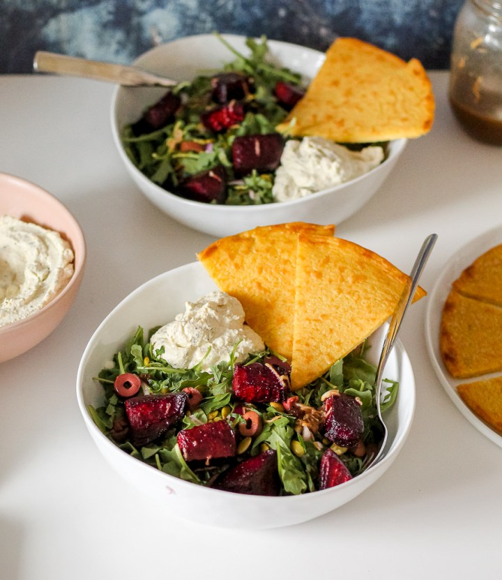 overhead shot of two bowls of roasted beets with arugula and whipped tofu and socca