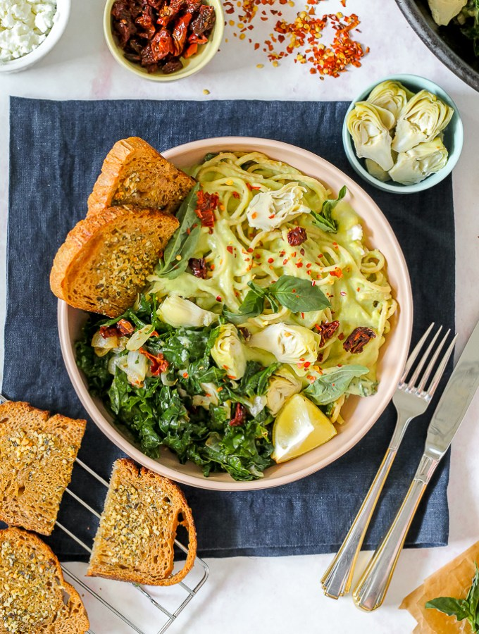 an overhead shot of a serving of the creamy white bean basil spinach artichoke pasta in a light pink bowl with garlic toast on the side