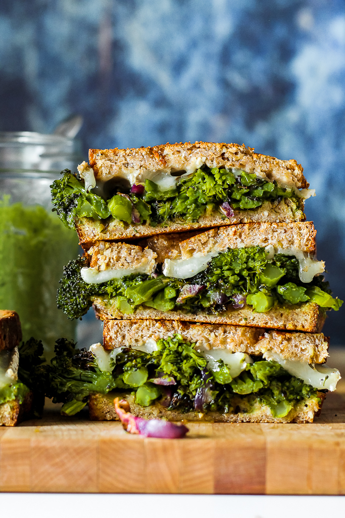 straight on shot of the grilled cheese sandwiches in a tall stack on a wooden board with a blue background