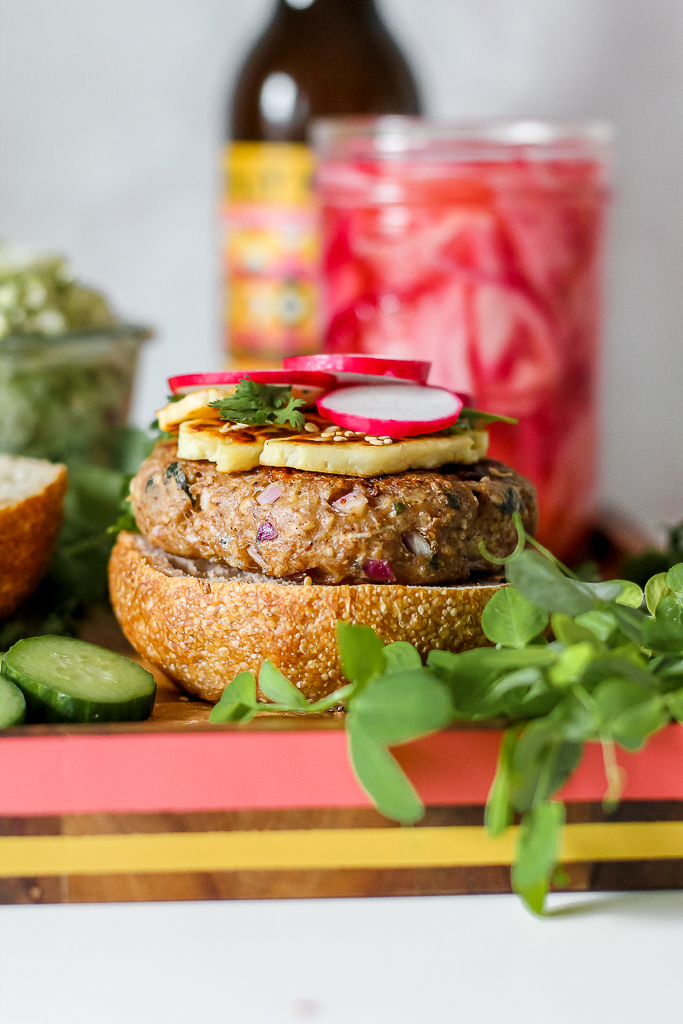 straight on shot of a shawarma turkey burger on a wooden board with a bottle of beer and a jar of pickled onions in the background