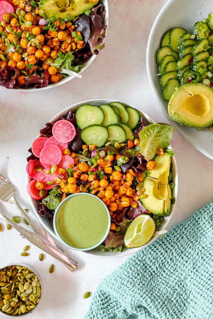 overhead shot of the smoky corn and chickpea salad in a serving bowl with a dish of the green goddess jalapeno dressing nestled in the salad