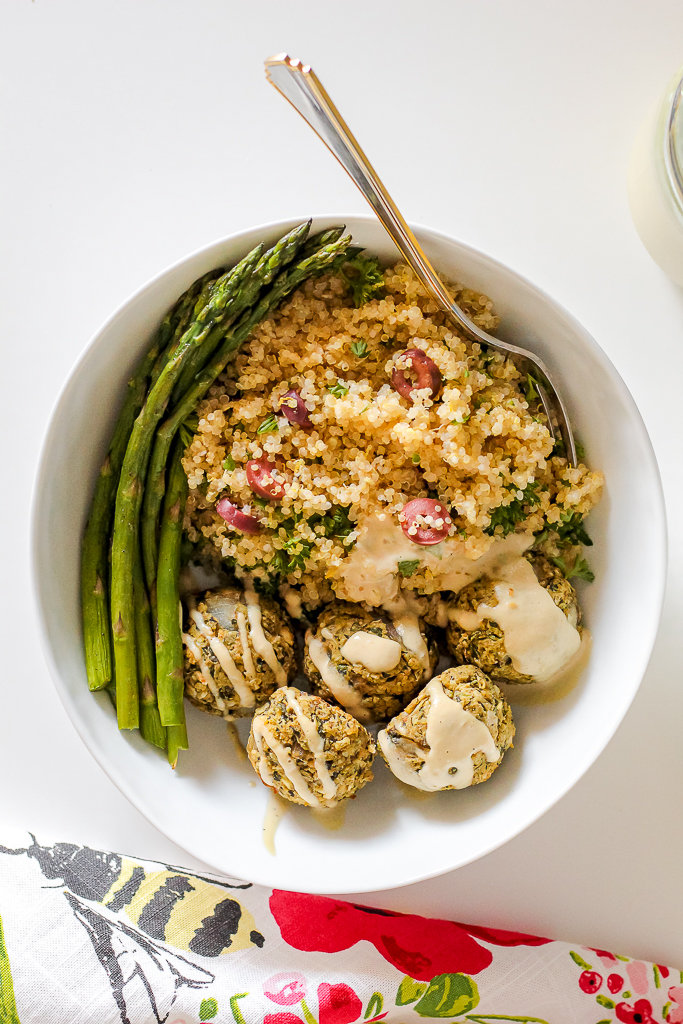 an overhead shot of a white bean spinach feta spanakopita style meatball bowl with lemon olive quinoa and roasted asparagus on white table