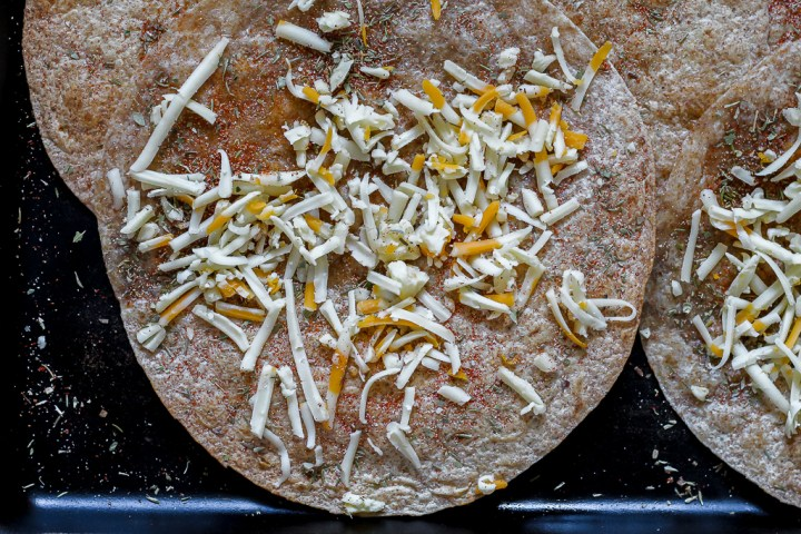 grated cheese on top of the tortillas