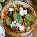 overhead close up of a chickpea tinga tostadilla on a wooden tray