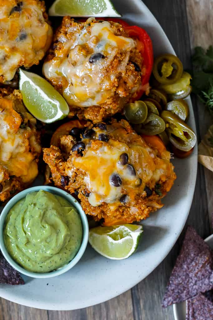 close up overhead shot of the chipotle chicken stuffed peppers on a blue platter with a dish of avocado crema beside
