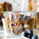 straight on shot of a dish of chocolate chunk pecan granola with milk being poured over top