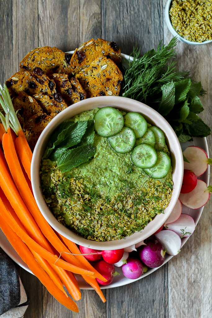 overhead shot of the green pea hummus topped with cucumber, mint, and cheesy pumpkin seed sprinkle surrounded by raw veggies and crackers