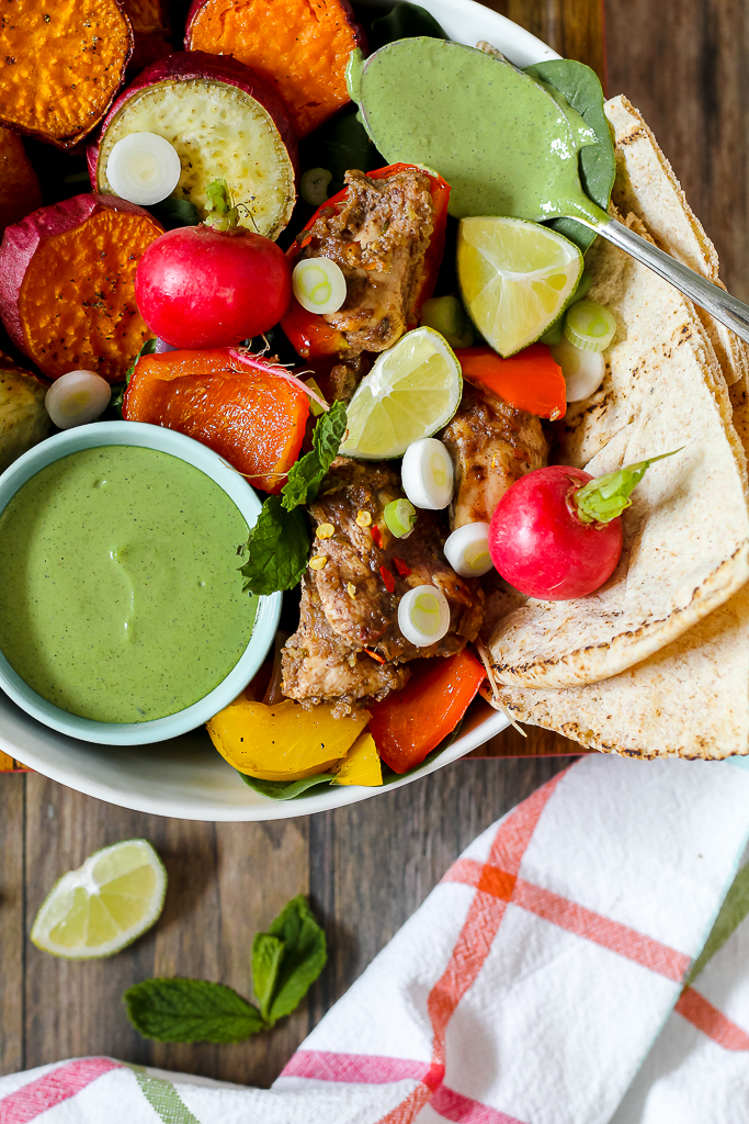 overhead photo of the jerk chicken and veggies in a white bowl with a pita bread