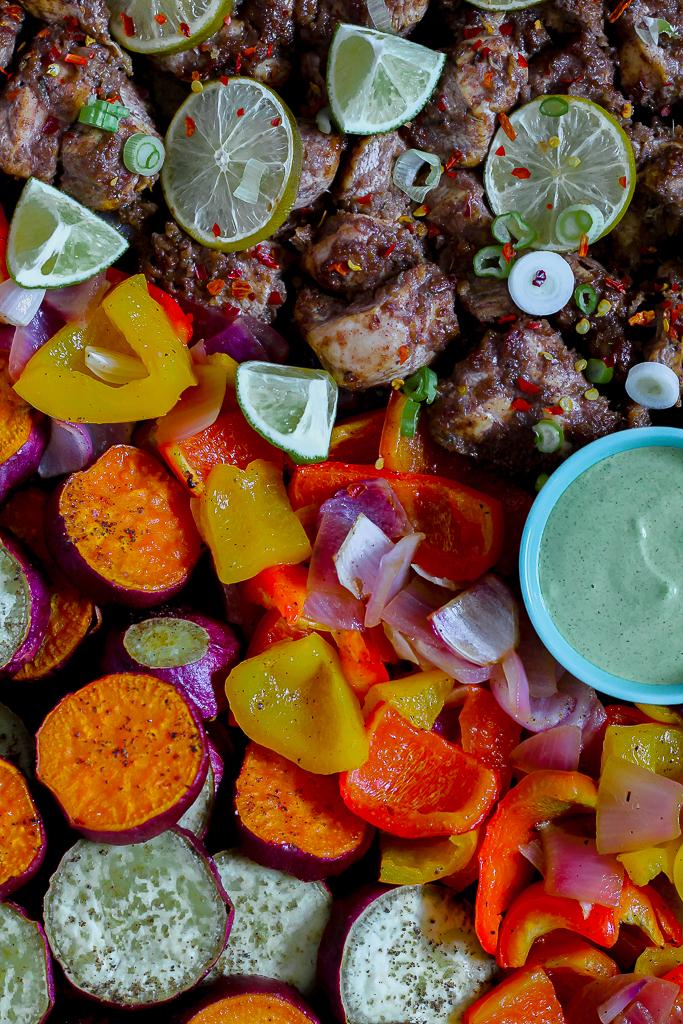 overhead shot of the sheet pan of veggies and jerk chicken
