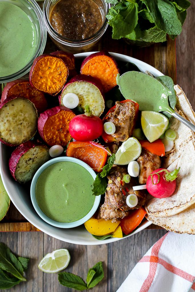 overhead shot of jerk chicken, veggies, pita, and hemp sauce in a bowl