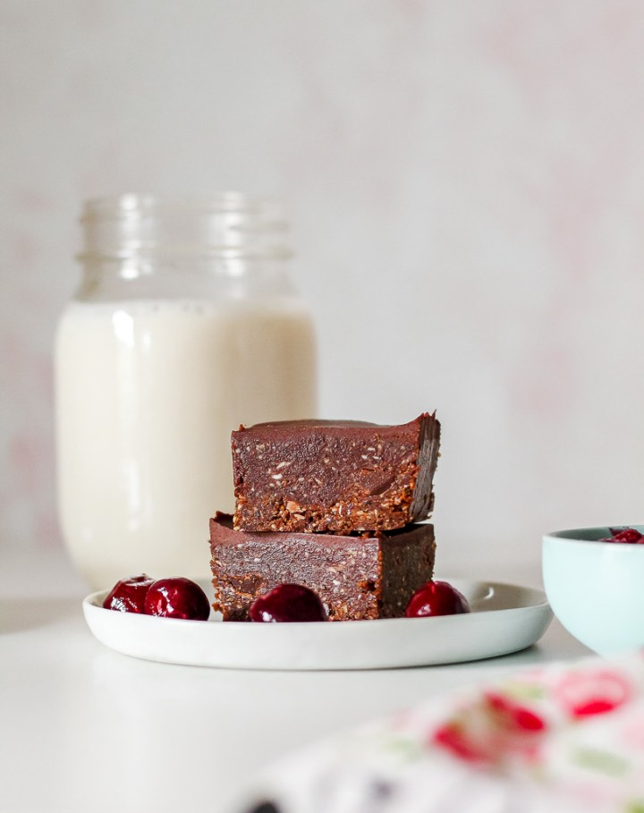 photo of two no bake vegan brownies on a plate with a glass of almond milk