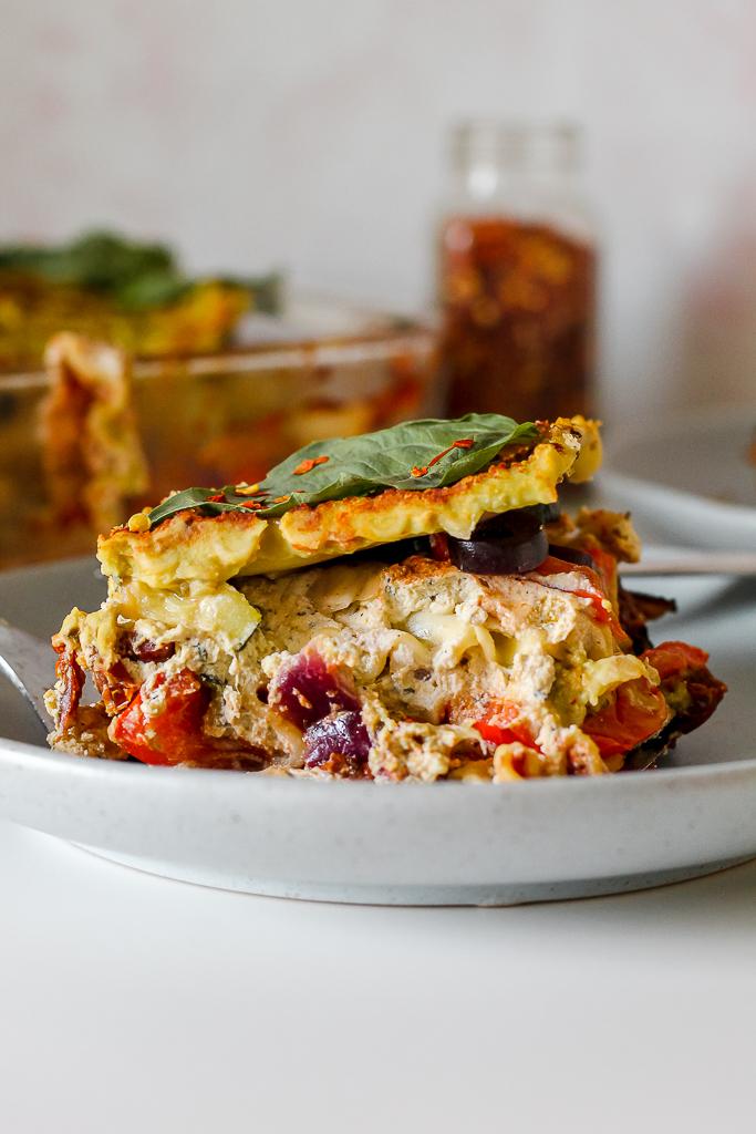 straight on shot of a slice of vegan white bean pesto cream lasagna on a blue plate