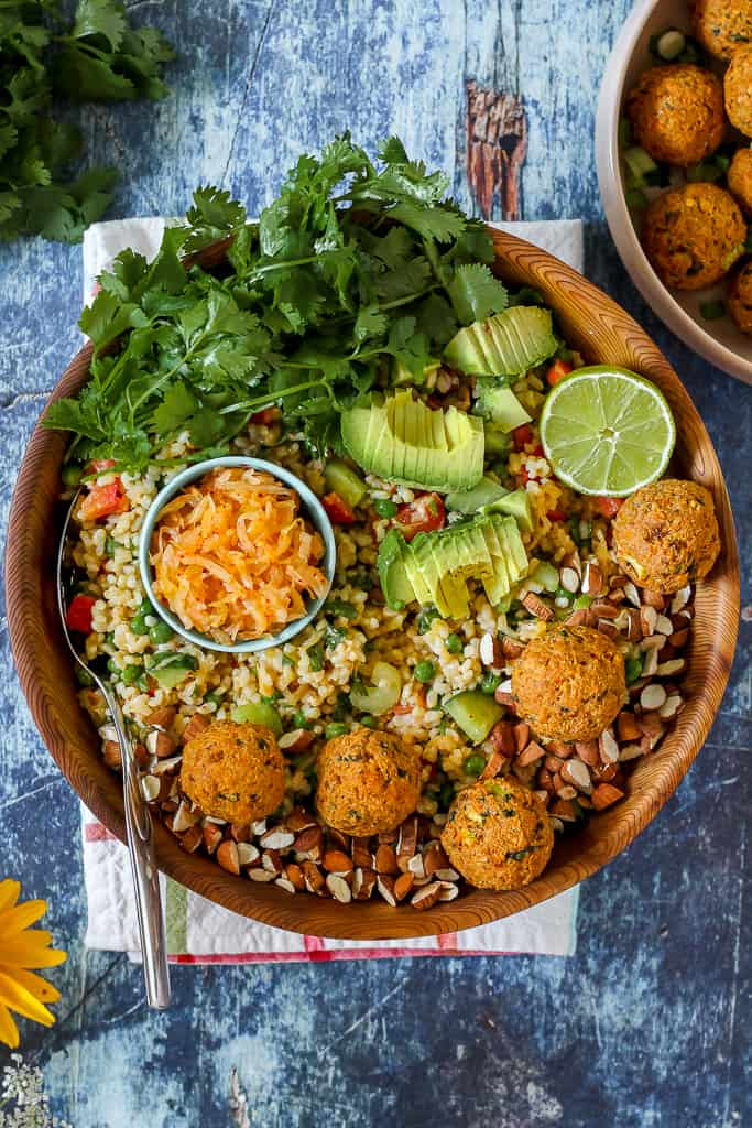 overhead photo of a big bowl of kimchi brown rice salad topped with Korean salmon balls