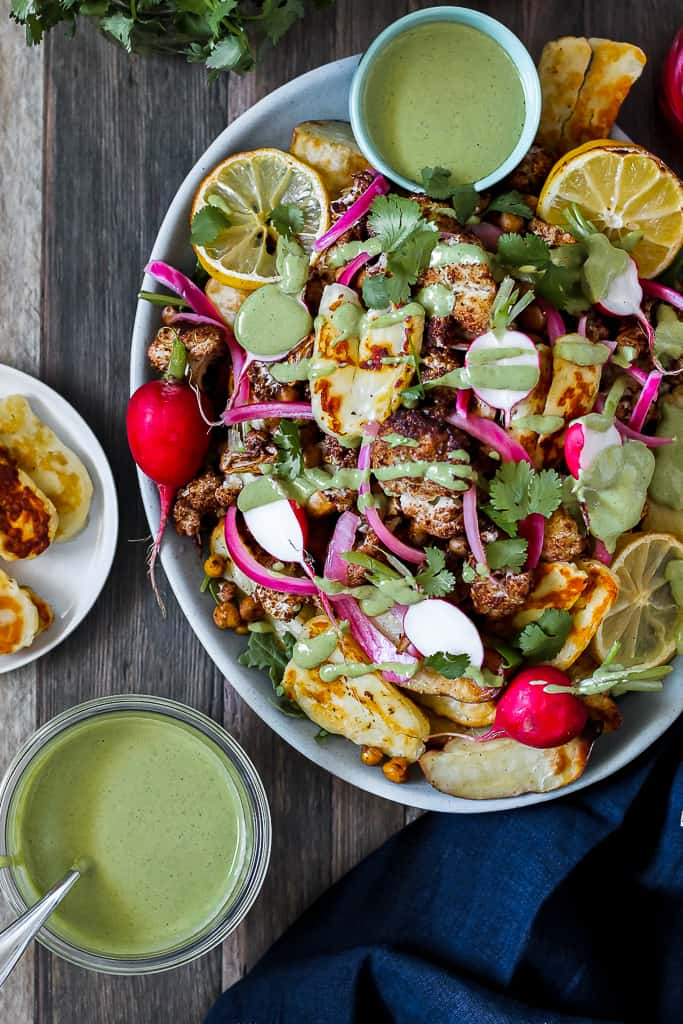 overhead shot of the loaded shawarma fries with cauliflower and chickpeas on a blue platter