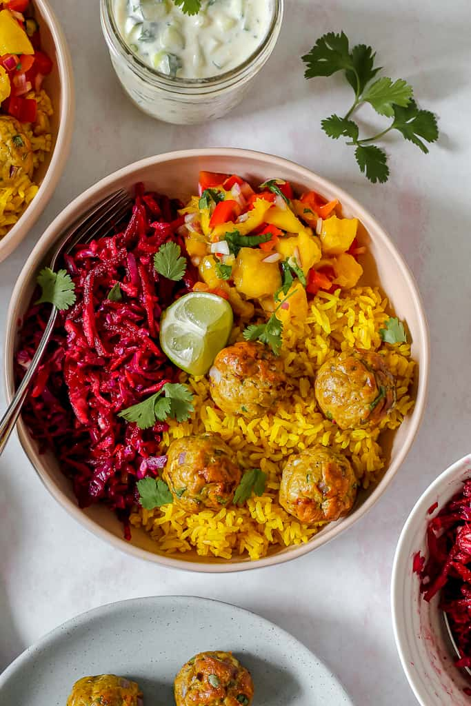 overhead photo of a masala chicken meatball bowl with turmeric rice, beet slaw, mango salsa, and the meatballs