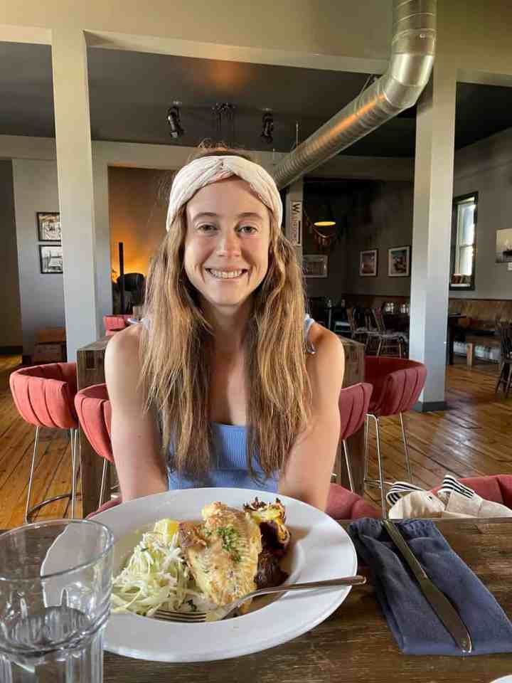 Allison sitting at Evermore Brewing in Summerside with a plate of food
