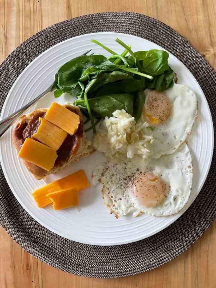 overhead shot of my lunch plate of cinnamon bun, eggs, spinach, and sauerkraut
