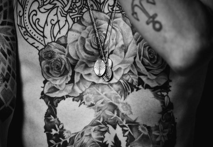 schwarz weiß foto von mann mit schmuck und tattoos