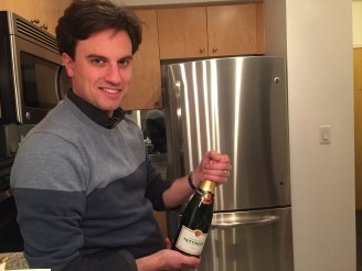 Tristan popping a bottle of bubbly