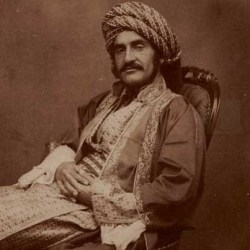 Fotografia preto e branco em tons de sépia. Hormuzd Rassam, utilizando turbante listrado, barba e bigode, reclinado sobre cadeira e vestido à moda otomana.
