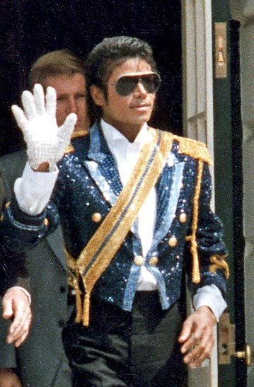 Michael Jackson, pictured in 1984, walking with hand up wearing sunglasses. Photo care of Wikimedia