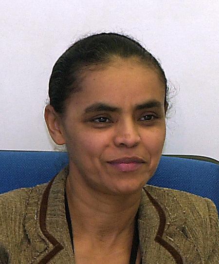 Mulher de cabelos negros presos atrás da cabeça, blazer beje, sorrindo levemente sentada em cadeira de encosto azul com parede branca atrás