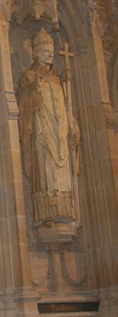 Stone statue of a man wearing a mitre and holding a staff topped by a cross. His other hand is held upright, palm facing out.