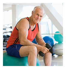 Elderly man with a dumbell sitting on an exerc...