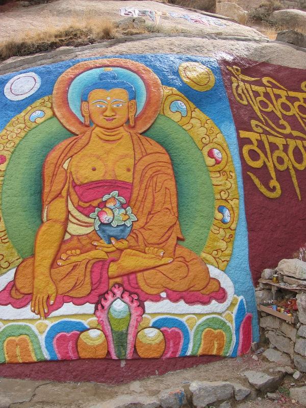 Buddha painted on a rock wall in Tibet - onwardtibet.org