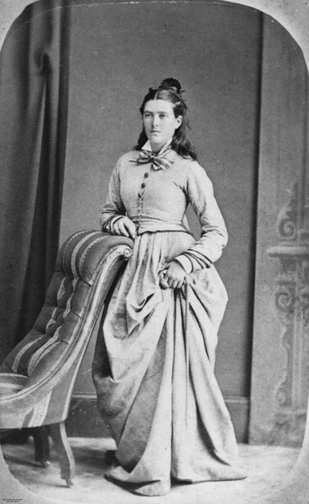StateLibQld 1 145647 Young woman dressed in a close fitting jacket and gathered skirt%2C posing next to a chair%2C 1870 1880 Portrait Collar Blouse