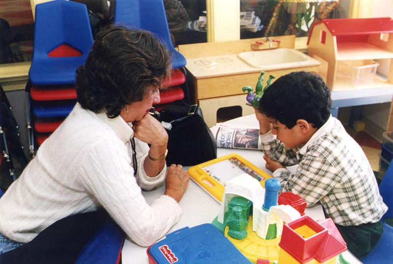 English: A special education teacher assists o...