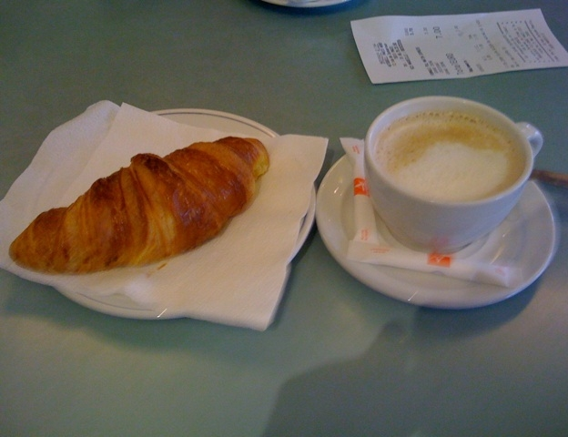 A meal with milk and a croissant.