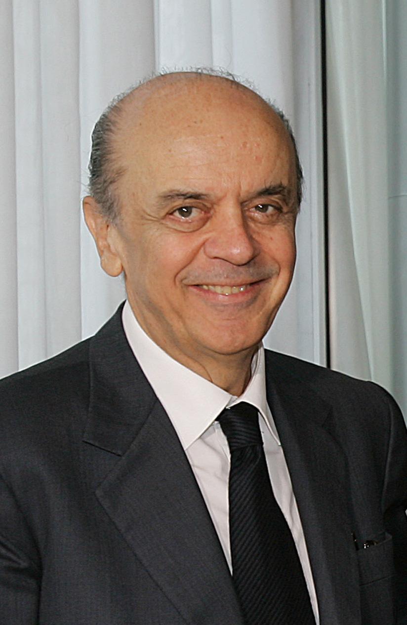 Homem calvo vestindo paletó e gravata pretos, e camisa branca, à frente de cortinas brancas