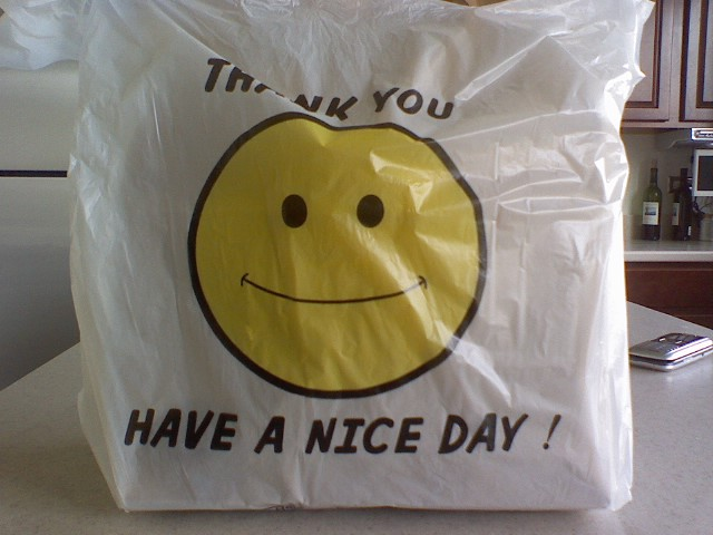 A bag with a smiley face design that bids the ...