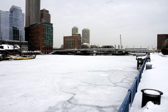 Snow covered bridge and river in Boston, MA