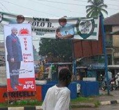 A man passes, in Freetown, posters for APC candidate Koroma (foreground) and the ruling SLPP ahead of presidential elections, 6 August 2007.