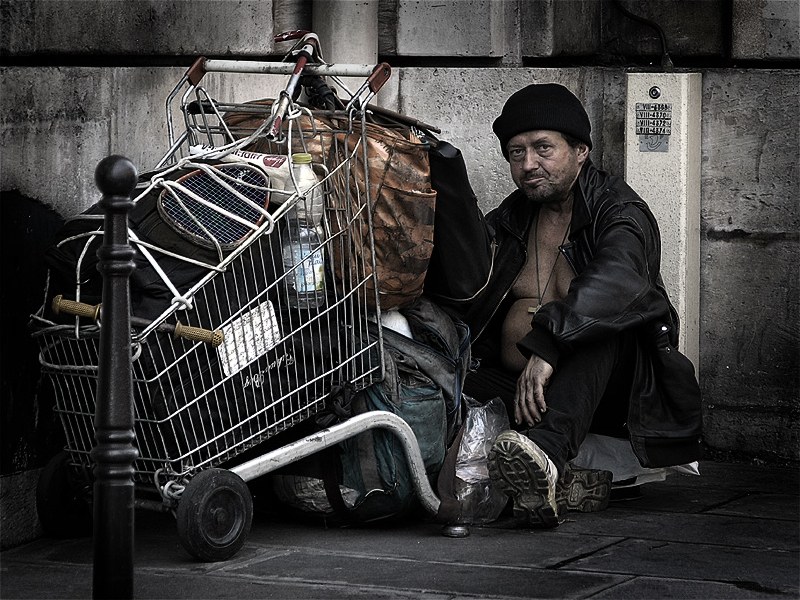Homeless man with shopping cart filled with his belongings.