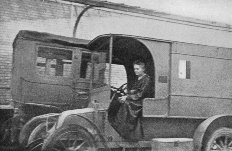 Marie Curie driving a little Curie