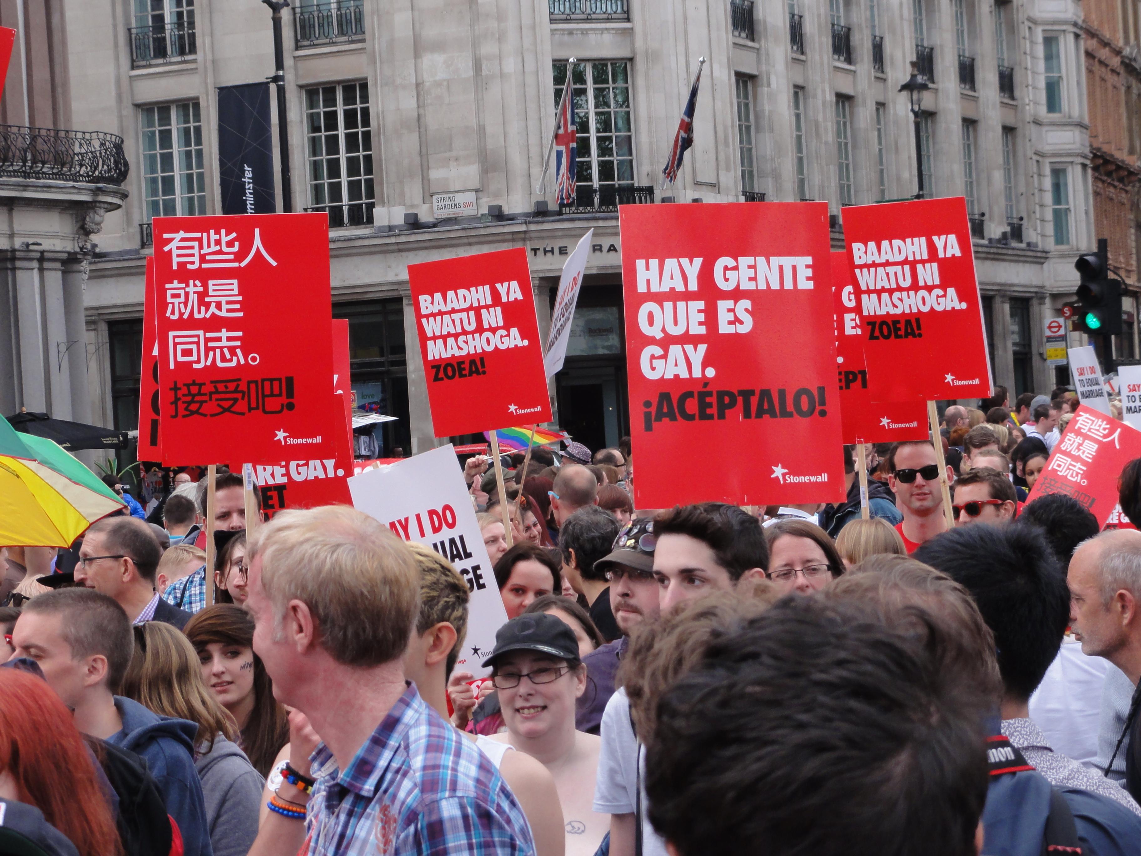 Pride-parad med skyltar på olika språk. Språklig mångfald FTW!