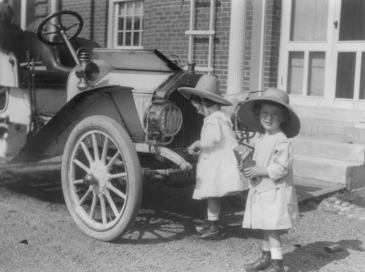 Small twin girls in front of 1911 Buick roadster