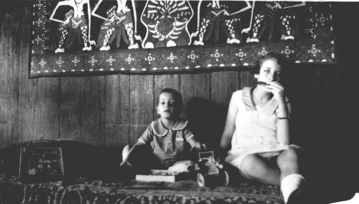 COLLECTIE TROPENMUSEUM Een meisje en een jongen met speelgoed op bed TMnr 60015810 Mainan Bocah Belanda VS Mainan Bocah Pribumi
